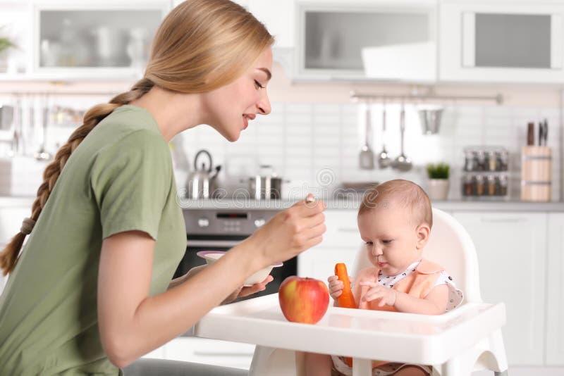 Femme alimentant son enfant dans le highchair à l'intérieur photographie stock