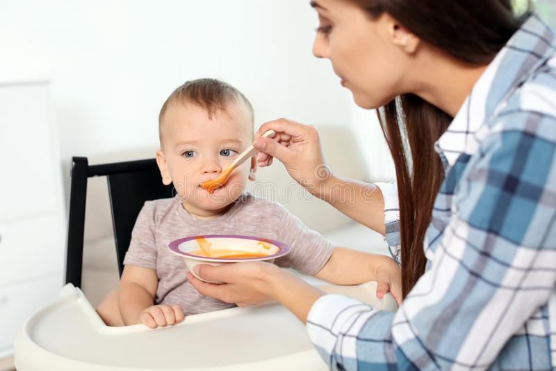 Femme alimentant son enfant dans le highchair à l'intérieur photos stock