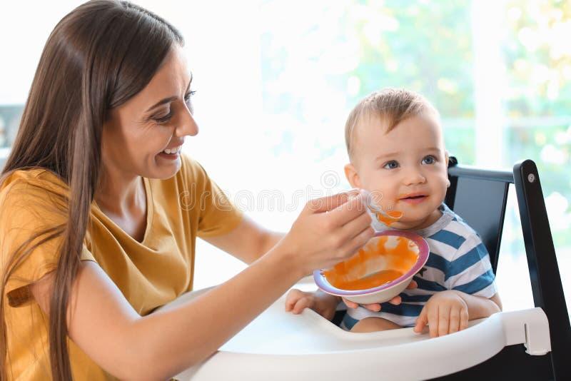 Femme alimentant son enfant dans le highchair à l'intérieur photo libre de droits