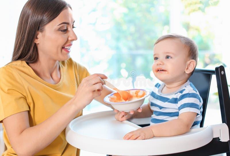 Femme alimentant son enfant dans le highchair à l'intérieur photos libres de droits