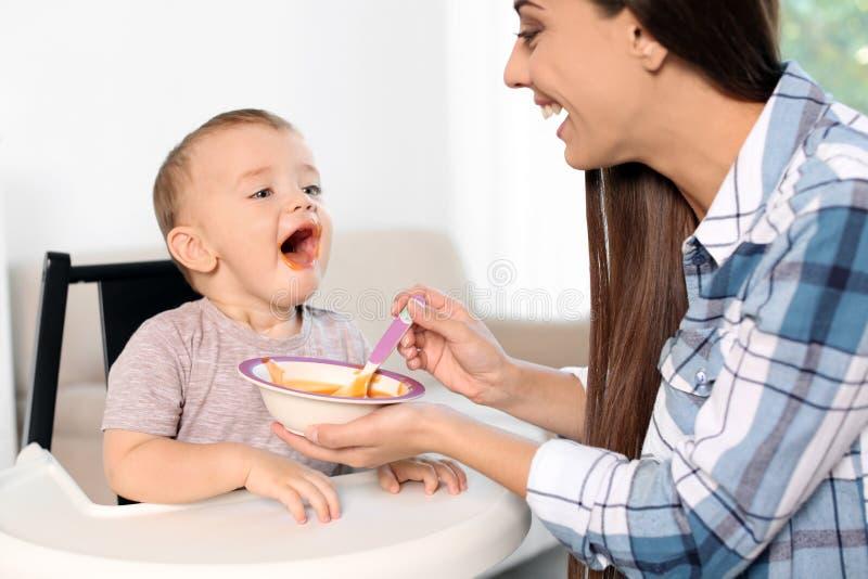 Femme alimentant son enfant dans le highchair à l'intérieur photographie stock libre de droits