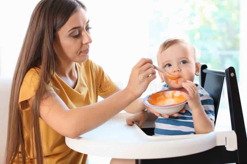 Femme alimentant son enfant dans le highchair à l'intérieur images libres de droits