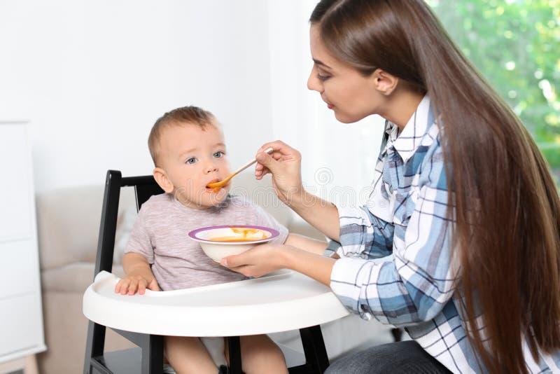 Femme alimentant son enfant dans le highchair à l'intérieur photo stock