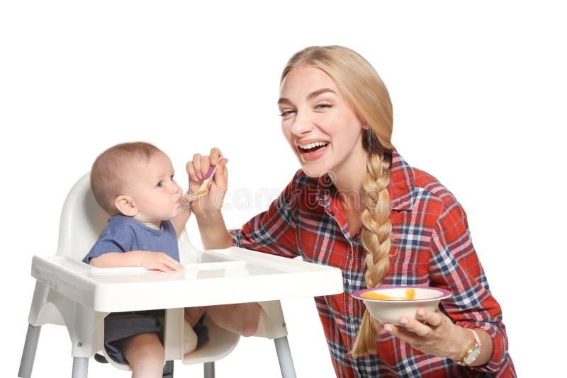 Femme alimentant son enfant dans le highchair photo stock