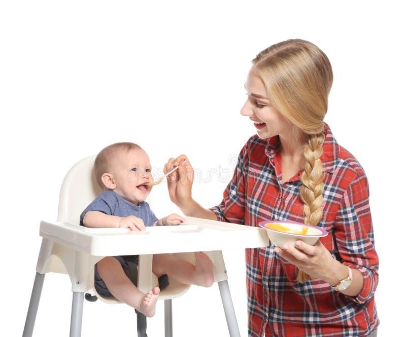 Femme alimentant son enfant dans le highchair photos libres de droits