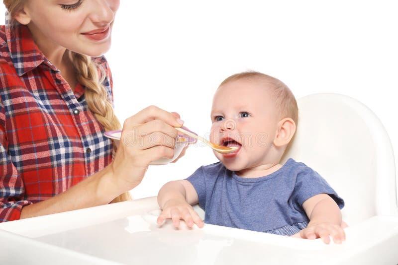 Femme alimentant son enfant dans le highchair photos stock