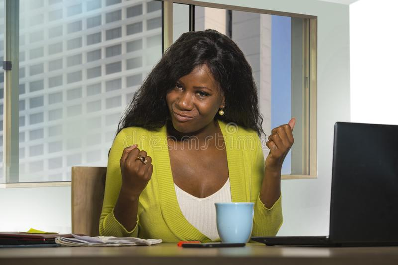 Femme américaine d'affaires d'africain noir souriant travail gai et sûr au bureau d'ordinateur célébrant le promoti de succès et  images stock