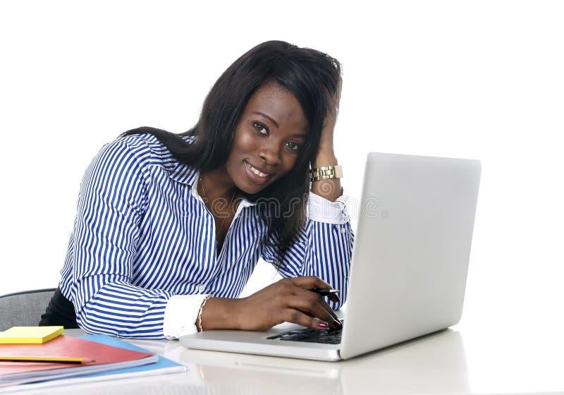 Femme américaine d'appartenance ethnique d'africain noir travaillant à l'ordinateur portable d'ordinateur au sourire de bureau he photographie stock libre de droits