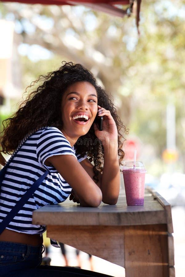 Femme américaine de jeune africana heureux riant et parlant au téléphone portable au café photos libres de droits