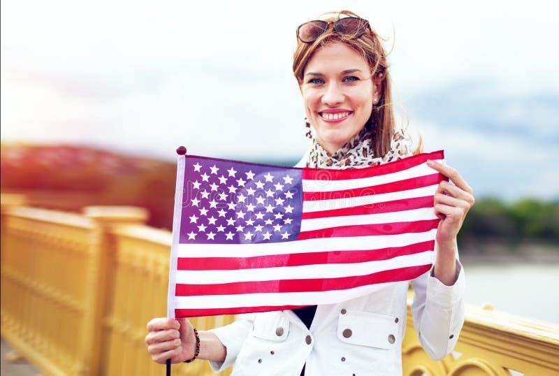 Femme américaine de jeune patriote avec le sourire toothy étirant le drapeau des Etats-Unis photographie stock