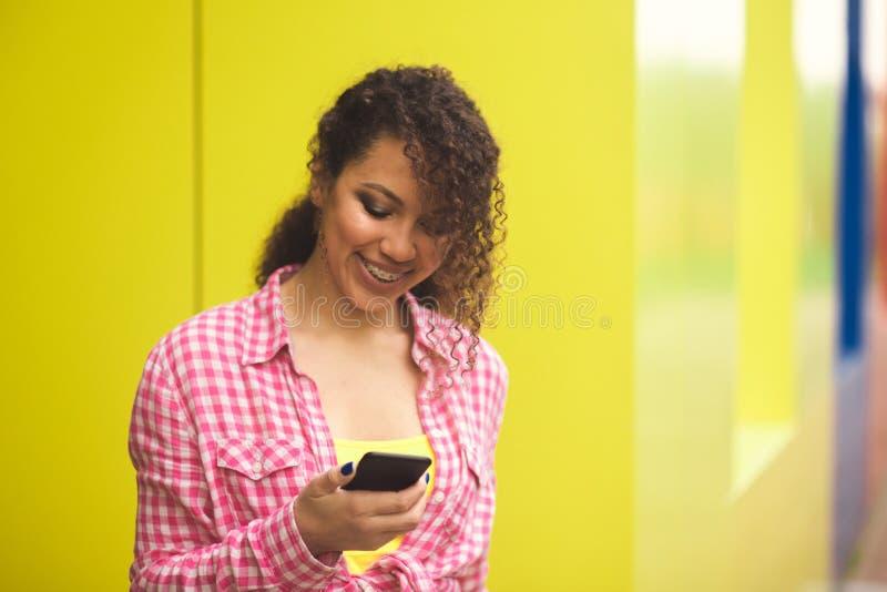 Femme américaine de l'Afrique recevant de bonnes actualités au téléphone dehors photo libre de droits