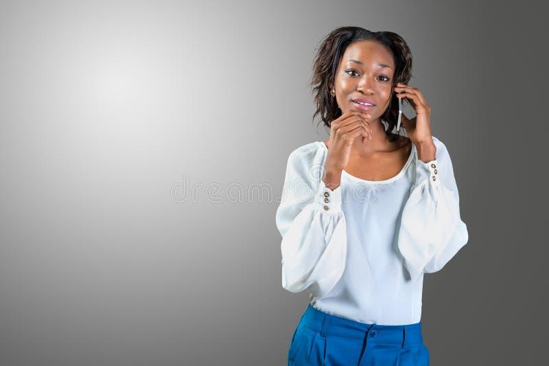 Femme américaine noire invitant le téléphone portable mobile photographie stock