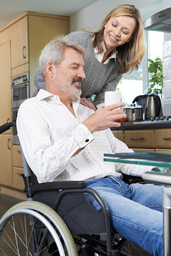Femme amenant l'homme dans la boisson chaude de fauteuil roulant à la maison photo libre de droits
