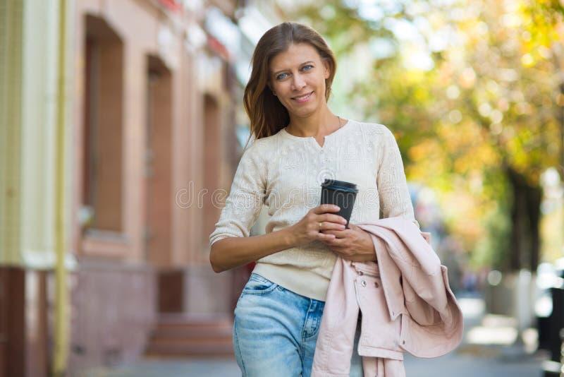 Femme 30 années marchant dans la ville un jour ensoleillé avec une tasse photo stock