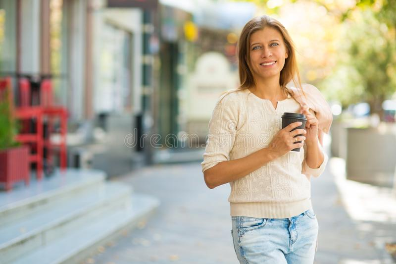 Femme 30 années marchant dans la ville un jour ensoleillé avec une tasse photographie stock