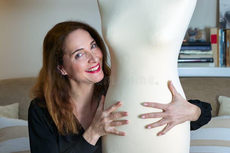 Femme 48 années, souriant et embrassant un mannequin regardant la caméra à la maison images libres de droits
