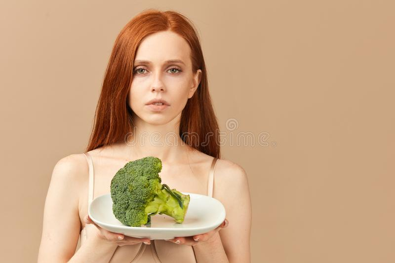 Femme anorexique dans le plat de participation de sous-v?tements avec le brocoli cru d'isolement dans le studio images libres de droits