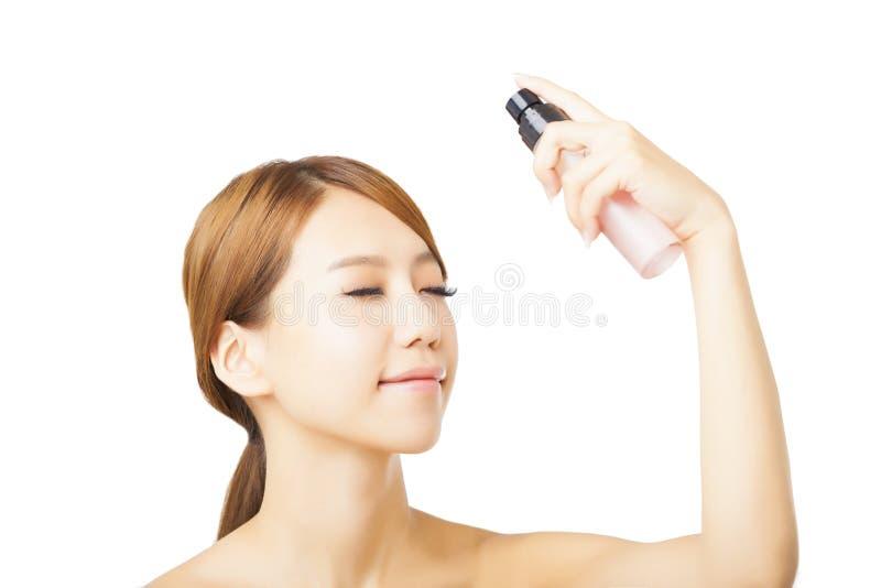 Femme appliquant l'eau de pulvérisation images stock