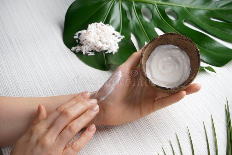 Femme appliquant la crème corporelle avec l'extrait de noix de coco images libres de droits