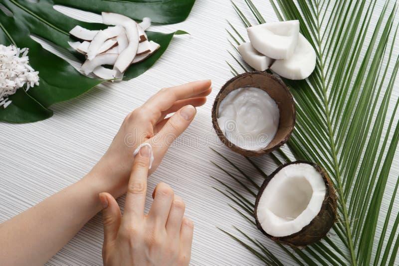 Femme appliquant la crème corporelle avec l'extrait de noix de coco photographie stock libre de droits