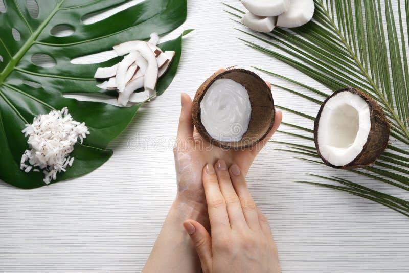 Femme appliquant la crème corporelle avec l'extrait de noix de coco photos stock