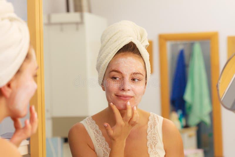 Femme appliquant la crème de masque sur le visage dans la salle de bains images stock