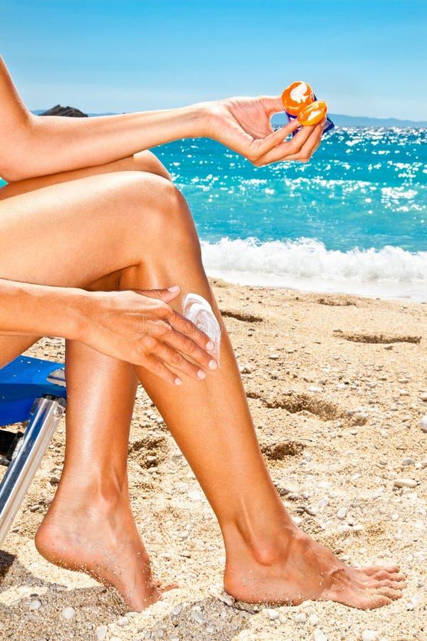 Femme appliquant la crème de protection du soleil à la plage photo libre de droits