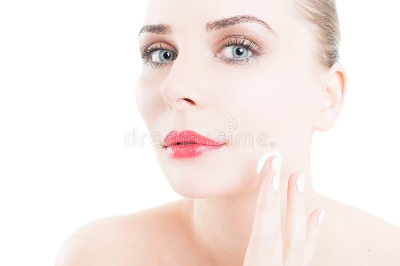 Femme appliquant la crème de visage sur le concept de soins de la peau photos stock
