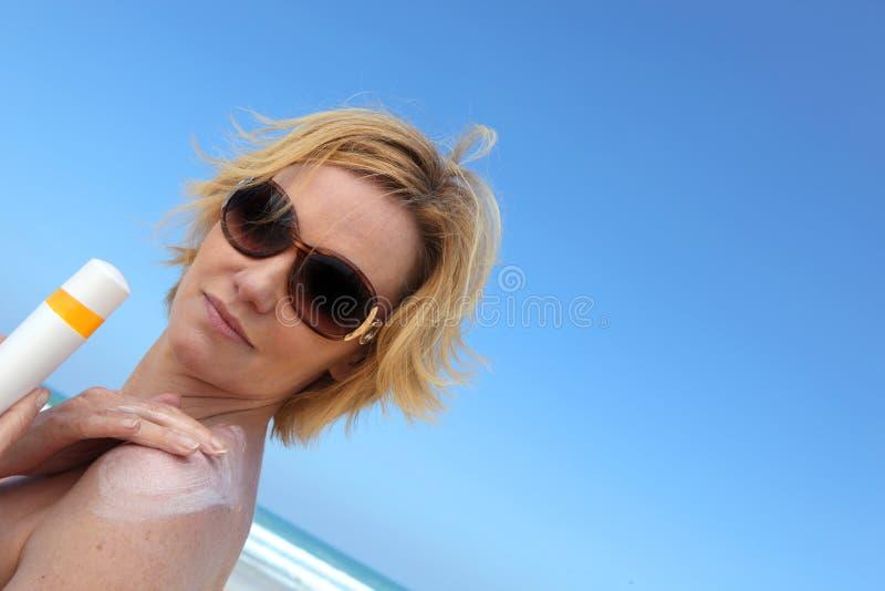Femme appliquant la crème du soleil images stock