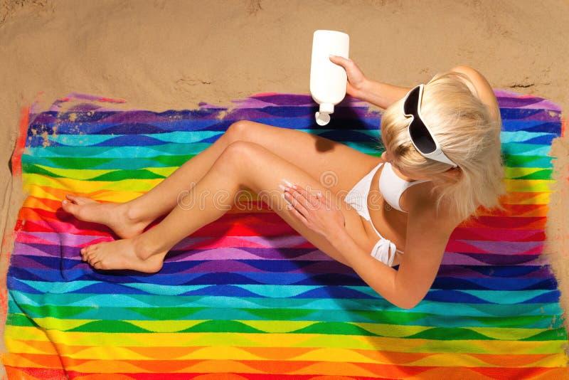 Femme appliquant la crème du soleil sur la plage photos libres de droits