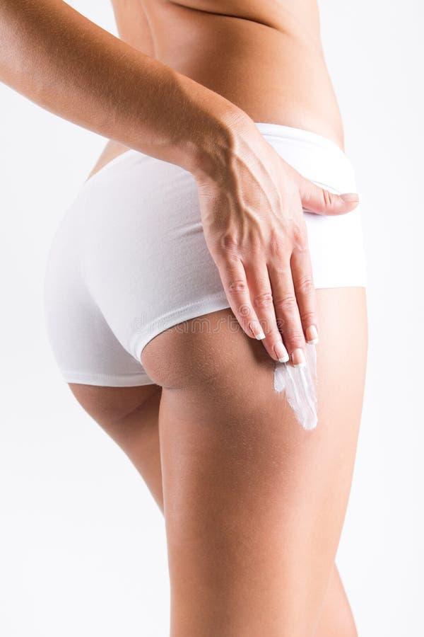 Femme appliquant la crème sur des jambes photo stock