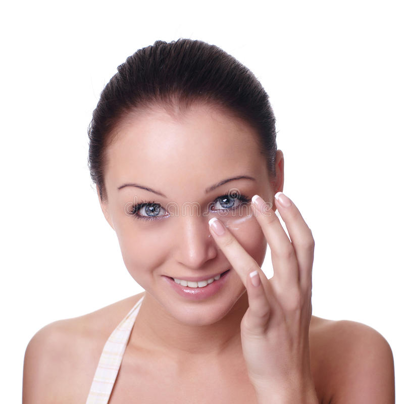 Femme appliquant la crème sur le visage photos libres de droits