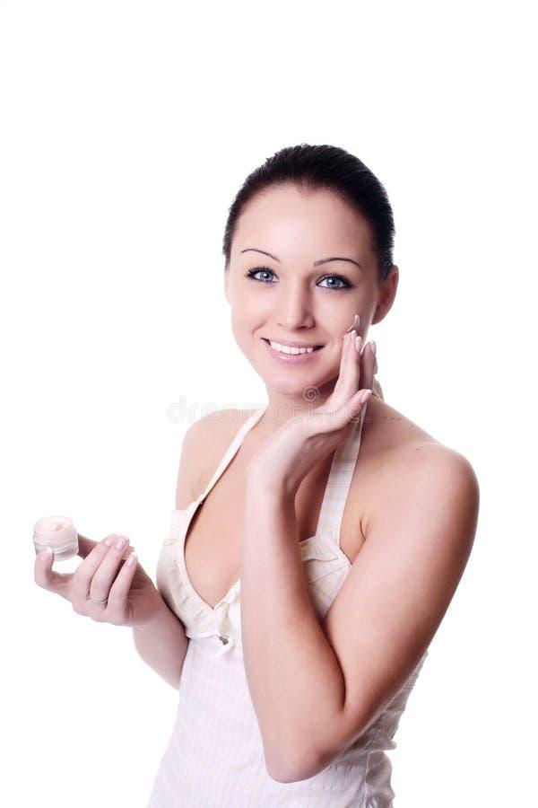 Femme appliquant la crème sur le visage photo libre de droits