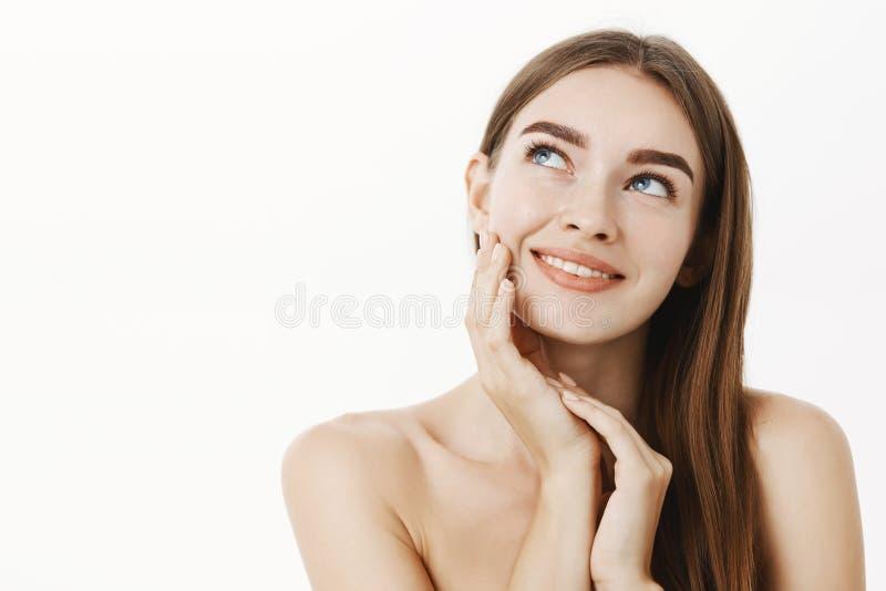 Femme appliquant la crème sur rêveur debout de peau de sentiment de visage et avec plaisir doux et tendres avec le résultat regar photographie stock