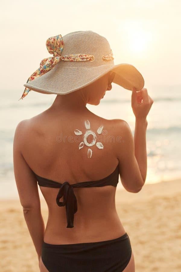 Femme appliquant la cr?me de protection solaire sur l'?paule bronz?e Soins de la peau Suncream de protection de Sun de corps image libre de droits