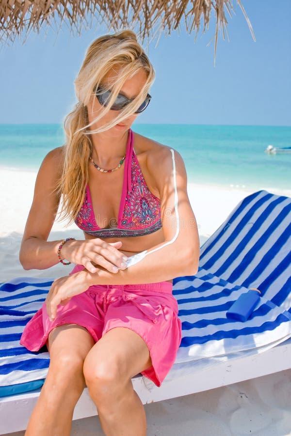 Femme appliquant la lotion de bronzage à une plage tropicale image stock