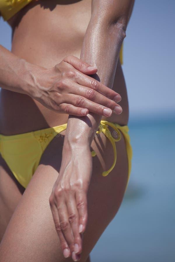 Femme appliquant la lotion de bronzage image libre de droits