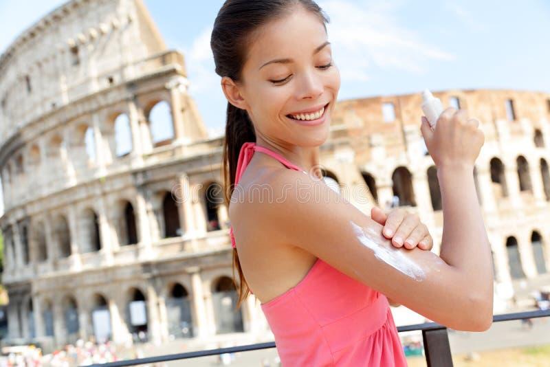 Femme appliquant la lotion de bronzage de protection solaire, Colosseum photos stock