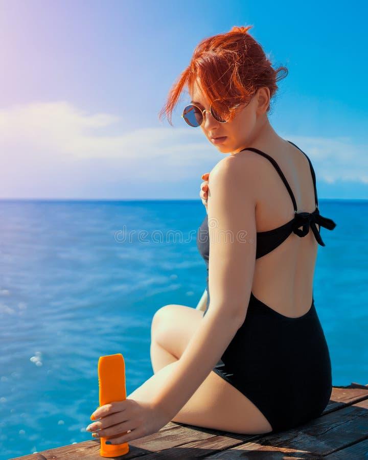 Femme appliquant la lotion de protection du soleil image stock