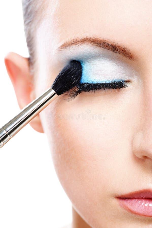 Femme appliquant la paupière de blusher photos libres de droits