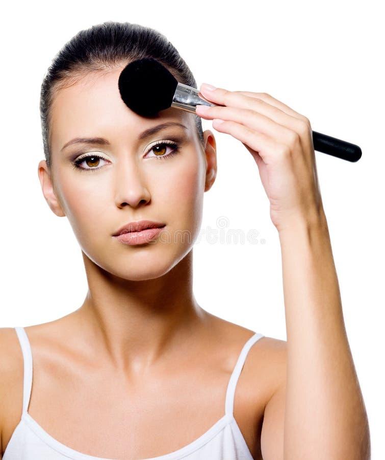 Femme appliquant la poudre sur le front avec le balai photographie stock libre de droits