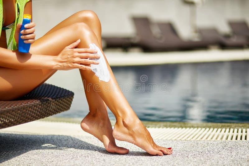 Femme appliquant la protection solaire sur ses jambes bronzées douces photographie stock libre de droits