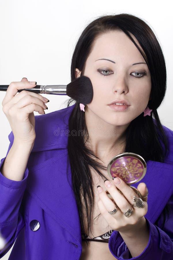 Femme appliquant le blusher image stock