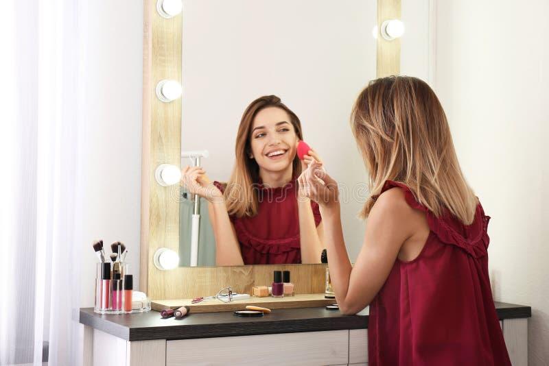 Femme appliquant le maquillage près du miroir avec les ampoules dans la chambre images stock
