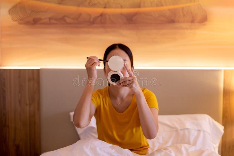 Femme appliquant le maquillage se reposant sur le lit photos libres de droits