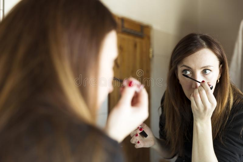 Femme appliquant le mascara noir sur des cils avec la brosse de maquillage dans la salle de bains photos stock