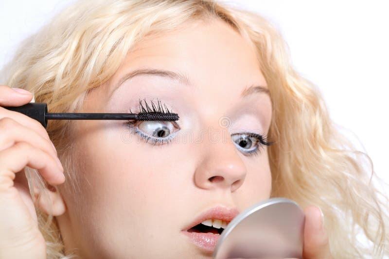 Femme appliquant le mascara noir sur son oeil images stock