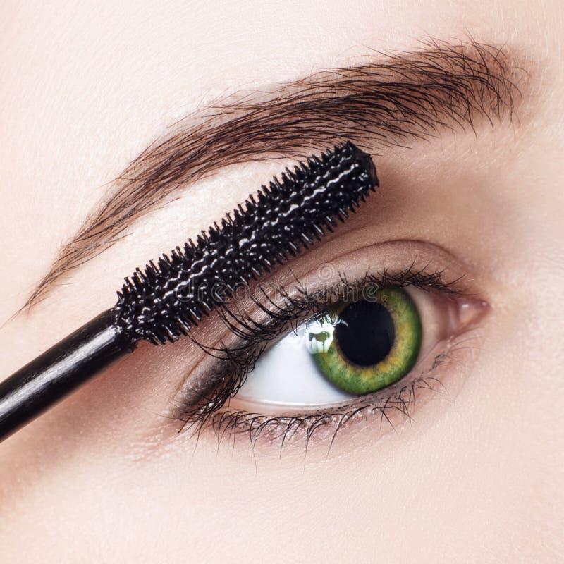 Femme appliquant le mascara sur des cils avec la brosse photographie stock