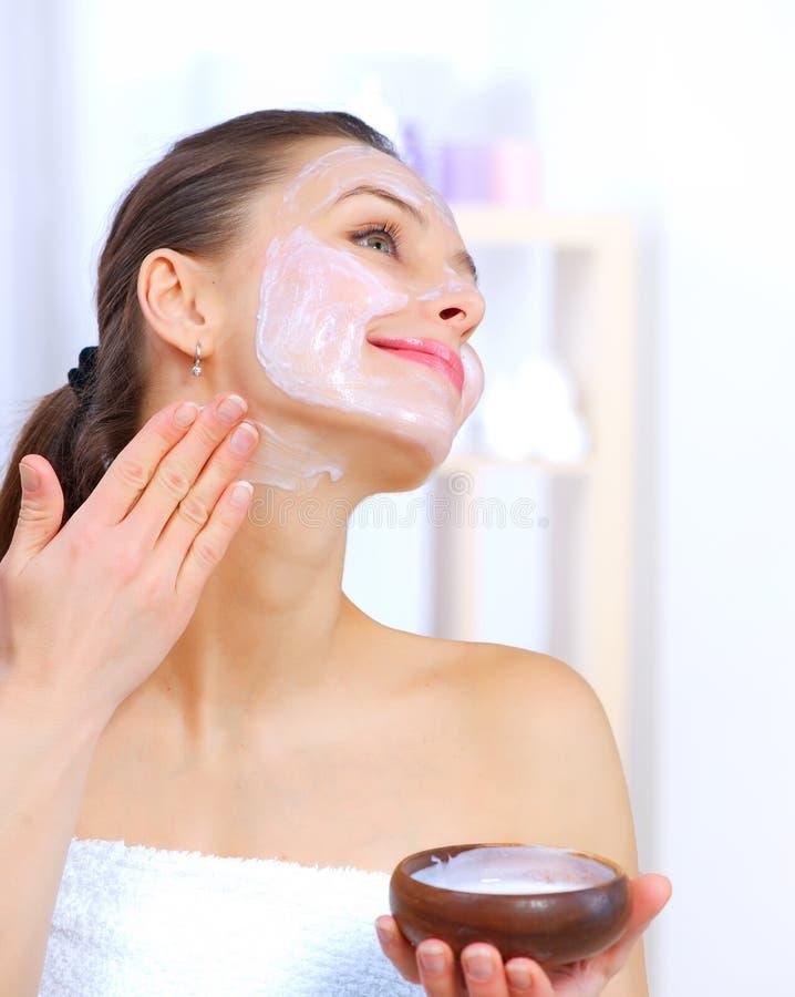 Femme appliquant le masque facial images libres de droits
