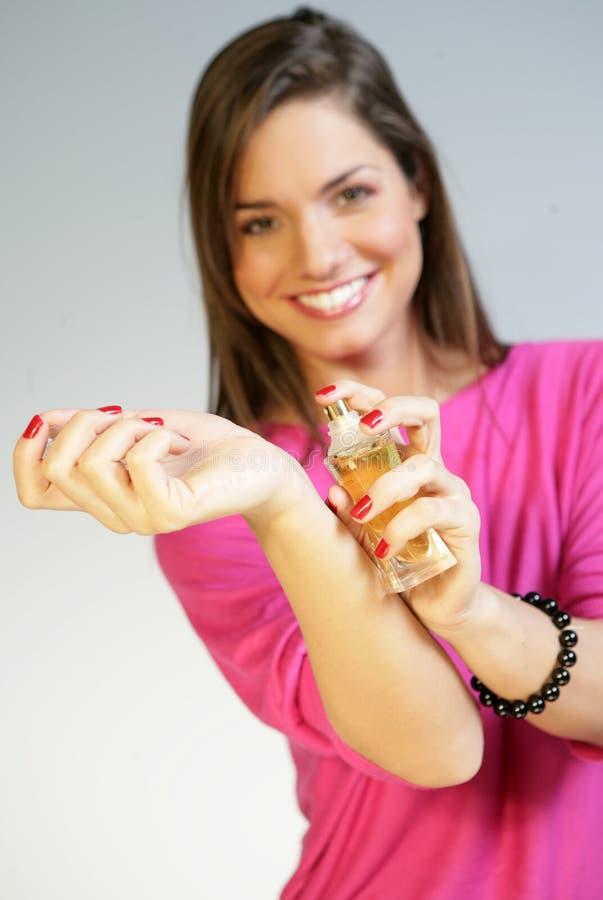 Femme appliquant le perfurme sur son poignet photographie stock